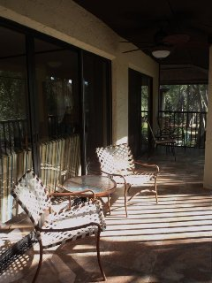 Enjoy the sun or shade under the fan on this tiled, screened lanai.