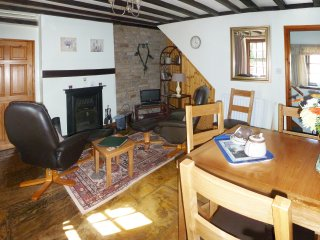 The dining room has extra comfy chairs and tv and a coal fire to sit round