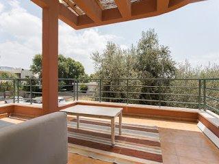 Large, shaded balcony with furnishings..