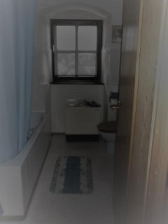 Badezimmer mit Fenster über den Dächern der Stadt