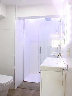 Un baño completo, moderno y con luces led integradas en espejo y ducha.