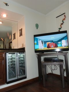 52 ' TV with cable chanels next to a wer t  bar and wine cooler
