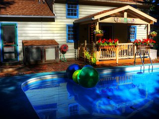 The Pool House with flowers on the porch and swimming pool