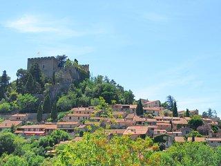Le village blotti au pied du château fortifié .