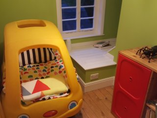 The child's bedroom features a car-bed and a single bed as well as a range of toys and books