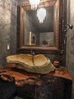 The half bath has a hand-carved stone sink atop a one-of-a-kind ancient redwood counter.