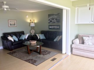 Comfortable furnishings and queen sleeper sofas in sunroom and living room.