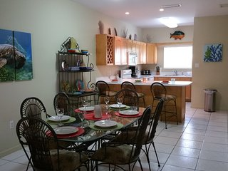 View of full kitchen with peninsula/bar stools and dining area.