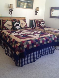 Second bedroom on main floor with a queen bed and twin bed.  Vaulted ceilings.