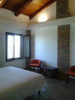 Piano primo, camera matrimoniale, con armadio e poltroncine.