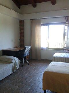 Prino piano, camera con tre letti singoli, scrivania e armadio..