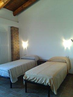 Piano primo, camera con tre letti, scrivania e armadio.