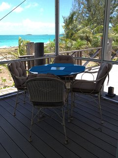 Screened porch with al fresco dining overlooking stunning turquoise sea