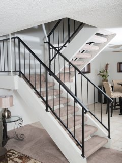 Staircase leading upstairs to both matching master suites.