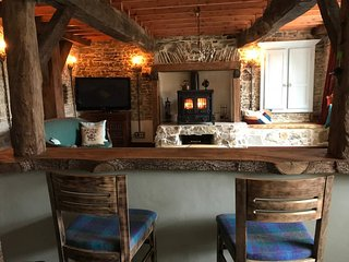 A view straight across the bar into the lounge with the large central wood-burner.