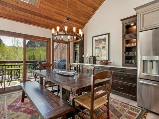 Dining room with seating for 6-8 features an elegant built in back bar with wine fridge.