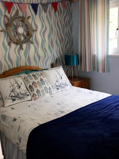 Main bedroom with double bed, bedside lamps, radio alarm, wardrobe and door to rear yard