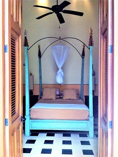 Four poster custom-made queen size bed opening to the courtyard with a pool view