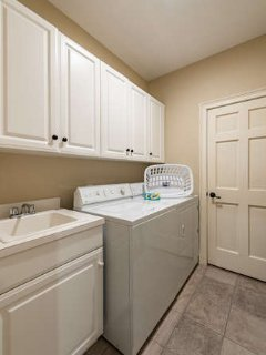 Separate laundry room with washer/dryer and utility sink for your use.
