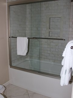The tub/shower has a tile surround and glass door.