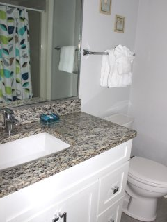 The hall bath has a granite counter, tile flooring, and shower.
