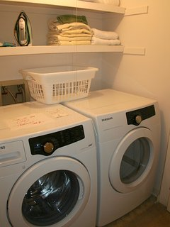 There is a front load washer and dryer in the hall.