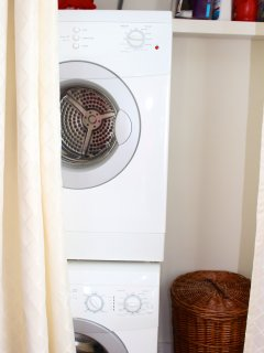The laundry area features a stacked laundry unit, ironing board, and iron.