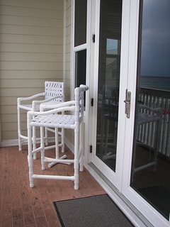Balcony has 2 chairs and a small table