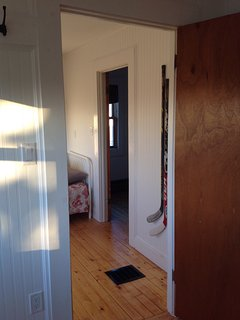 The view from 1 bedroom back through another to the upstairs landing. Hockey sticks on wall..Canada!