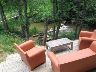 Patio seating overlooking rushing creek