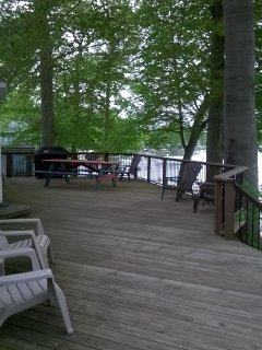 Deck with weber grill, deck chairs, and good place to set up cornhole.