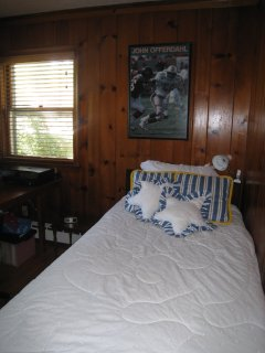 First floor bedroom with twin bed and office desk.
