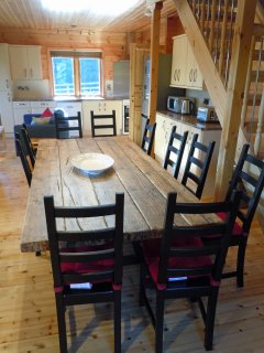 The dining table with 10 chairs and kitchen