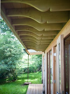 The beautifully carved eaves creating a covered walkway at the front of the cabin.
