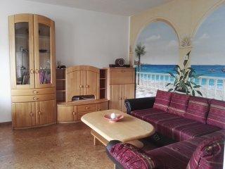 Wohnzimmer, mit Schlafsofa. Im Schrank befinden sich Spiele und SAT-TV.