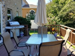 Wooden large deck with gas BBQ grill.