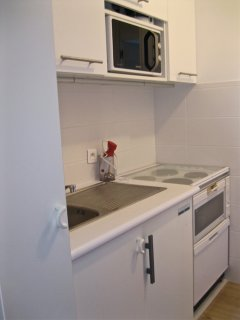 Galley kitchen with 4 plate electric hob, oven, microwave, fridge and dishwasher. Plenty of storage.