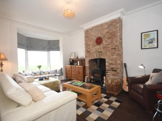 Spacious and comfortable lounge with sweeping views over cricket/rugby ground and multi-fuel stove