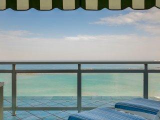 Terraza sobre el mar con toldo