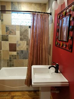 Full bath with tub/shower.  Mosaic of reclaimed tiles.