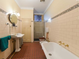 Massive bathroom with laundry and vintage fixtures and furnishings