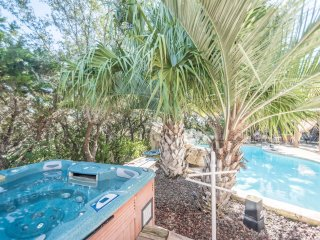Hot tub is located behind pool and next to pool cabana.