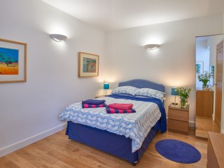 Spacious, light double bedroom with two windows, bed, chest of drawers,wardrobe,  bedside cabinets.