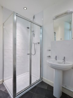 All white bathroom with large shower, wash hand basin, mirror with shaving point and toilet.
