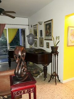 Art filled living room.  Piano is over 100 years old!