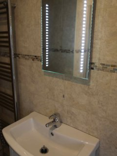 Bathroom with 'walk in' shower, toilet, sink and towel rail