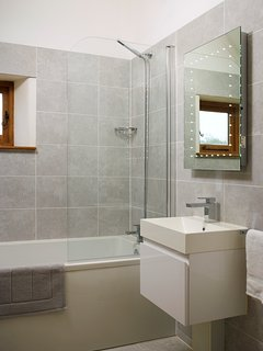 Modern en suite in the Master Bedroom with full size bath with shower, WC and wash hand basin.
