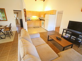 There's a full kitchen, a dining area, and a living area with flat screen TV and comfortable couch.
