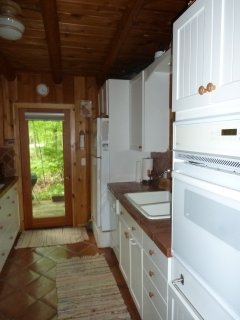 Galley-like kitchen has everything you need to cook & clean, large windows, door leads to b-b-q deck