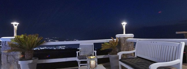 Seating area next to the swimming pool at night overlooking Mykonos town.